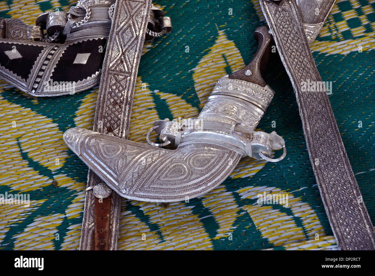 Engraved silver belts and khanjars (daggers) for sale in market, Sinaw, Oman - Stock Image