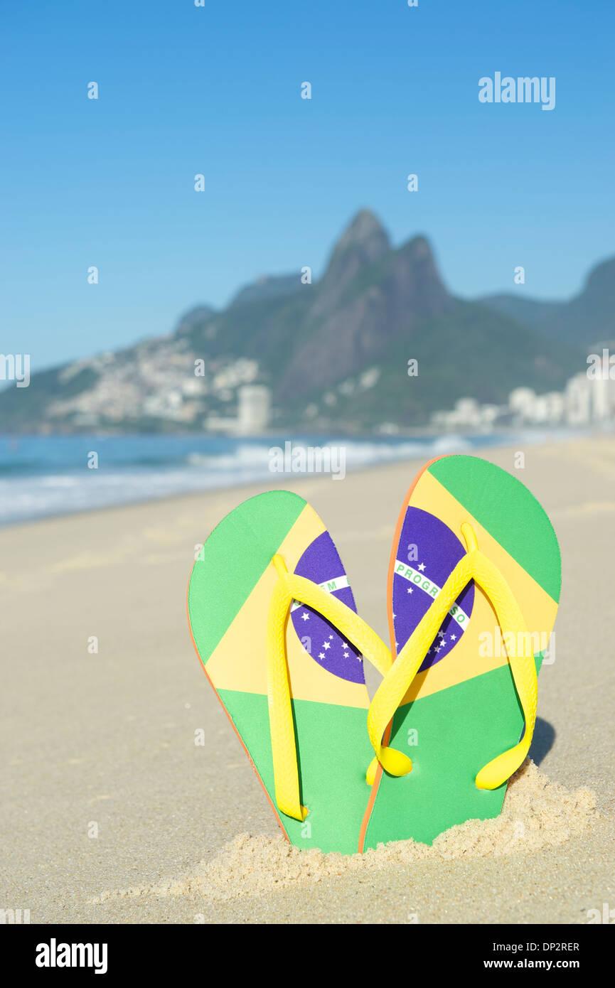 6ee6e5bd4af Brazilian flag flip flops sandals stuck in the sand on Ipanema Beach against  a backdrop of Dois Irmaos Mountain Rio de Janeiro