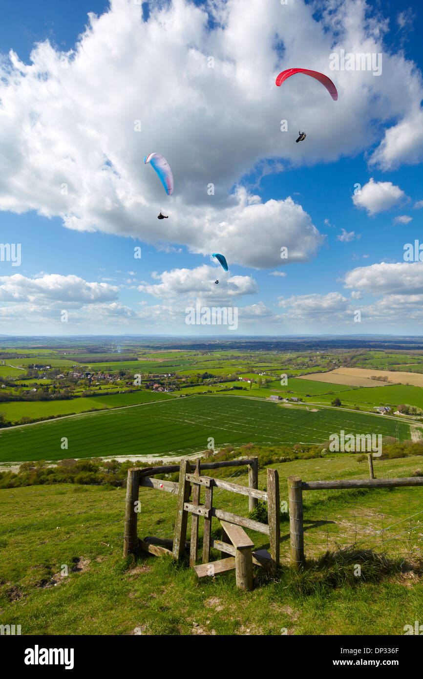Paragliders enjoying the scenery across the South Downs, West Sussex. Flying high above Devil's Dyke. - Stock Image
