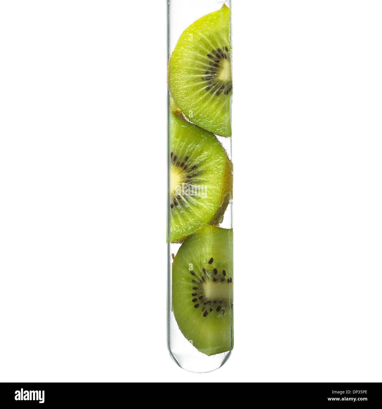 Kiwi slices in a test tube - Stock Image