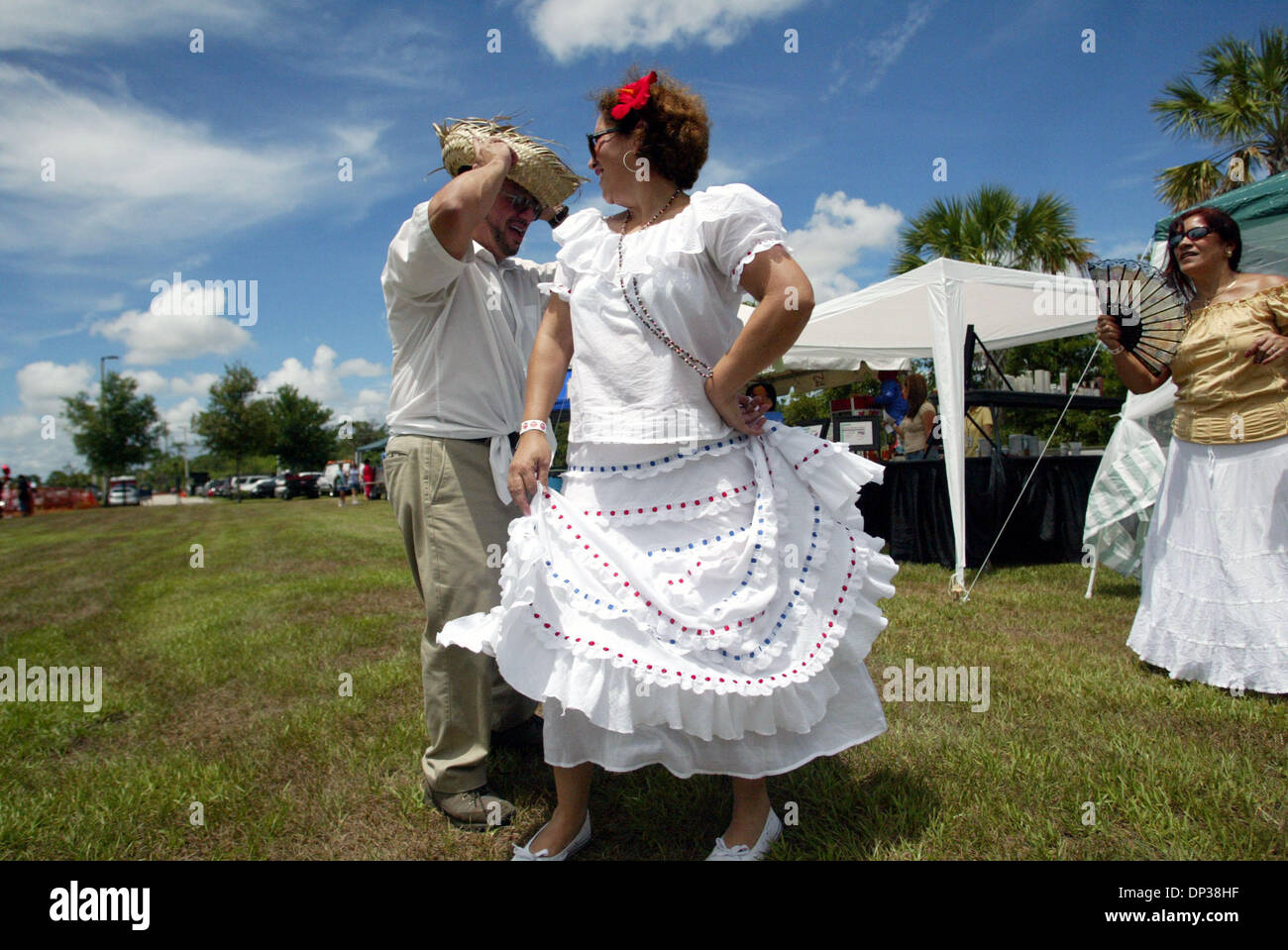 Jun 24, 2006; Port St. Lucie, FL, USA; Israel Pabon, dances with his wife Maria, at the San Juan Festival and Business Expo at the South County Regional Sports Stadium, while a friend Ana Villanueva, cq, tries to keep cool in the sun. The festival was sponsored by the Puerto Rican Association for Hispanic Affairs. The Pabons met when they were in high school and have always danced. - Stock Image