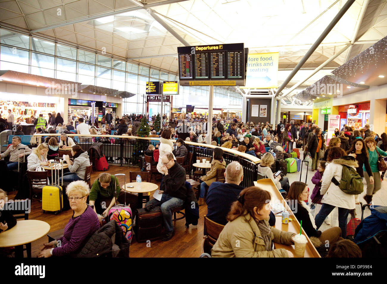 Stansted airport departure lounge; crowded with people travelling; Essex, England UK - Stock Image