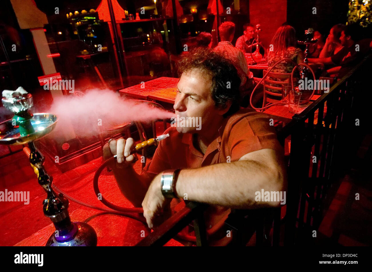 Jun 29, 2006; Sacramento, CA, USA;  Kasbah Lounge owner Paul Ringstrom smokes a hookah at his Kasbah Lounge in Sacramento Stock Photo