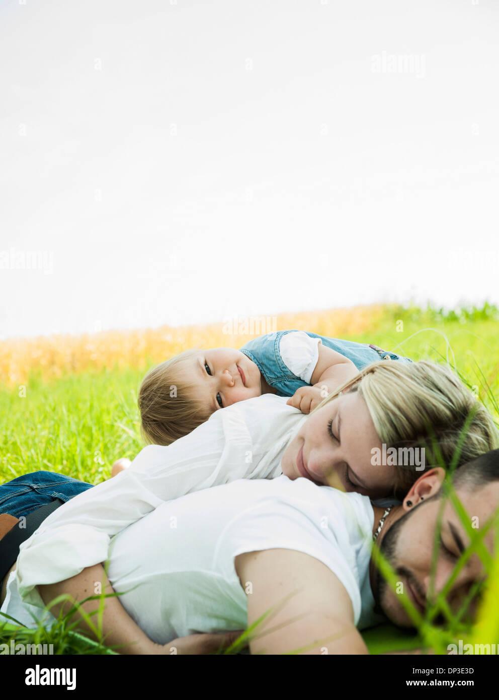 Family Sleeping in Grass, Mannheim, Baden-Wurttemberg, Germany Stock Photo