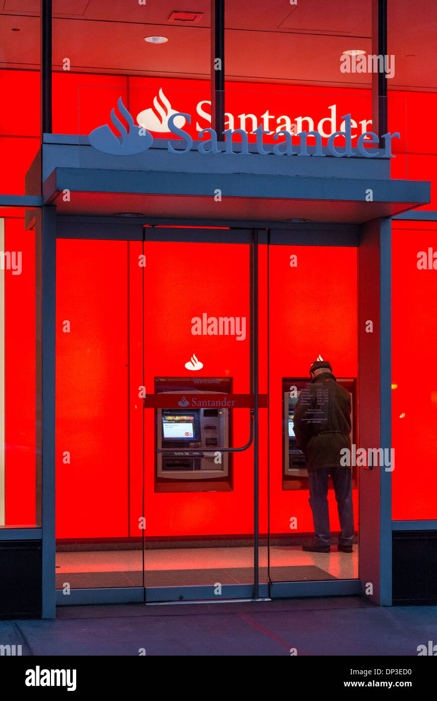 Man Using ATM At Banco Santander Branch Dusk NYC USA