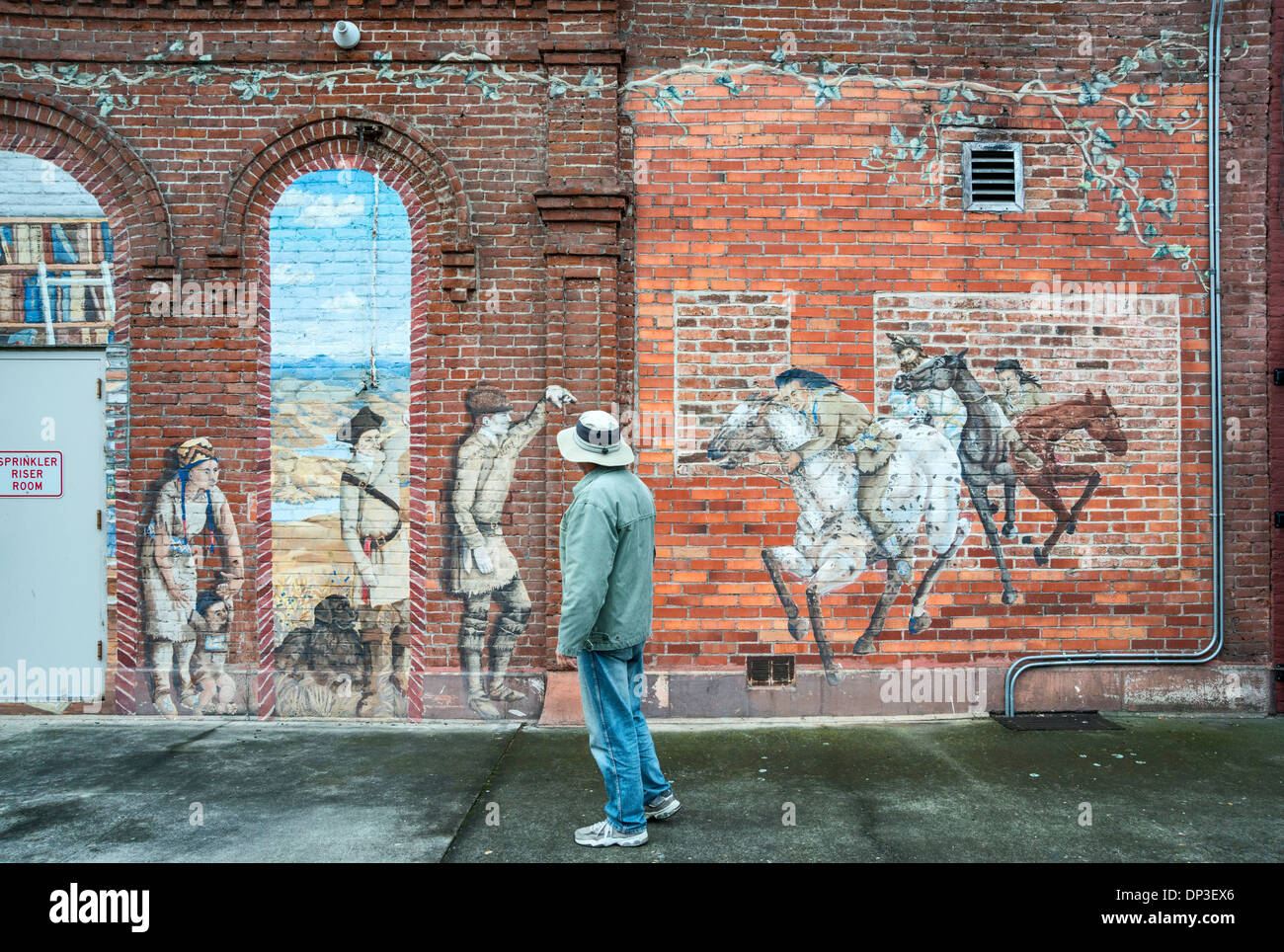Passerby at mural at LCSC Center for Arts and History on D Street in downtown business district of Lewiston, Idaho, USA - Stock Image