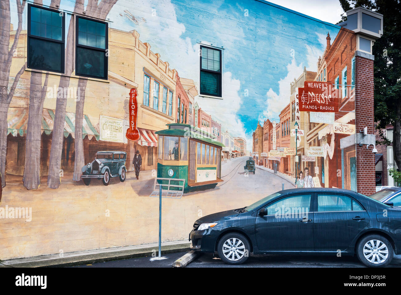Modern car parked at mural by Peter Goetzinger, showing Main Street in 1930s, Lewiston, Idaho, USA - Stock Image