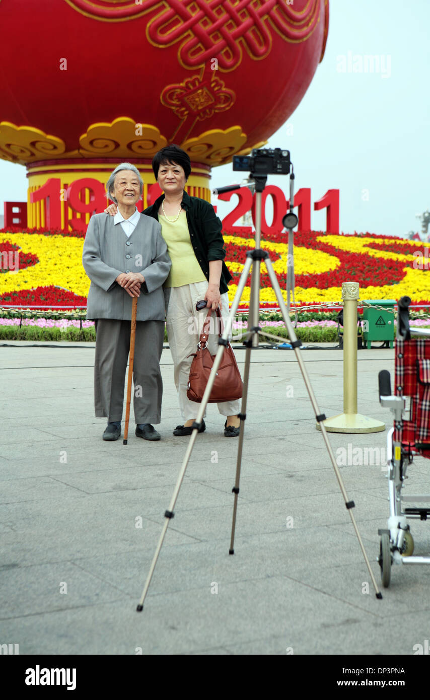 Old and young Chinese taking a self portrait in front of a communism commemorative display, Tiananmen Square, Beijing, China. - Stock Image
