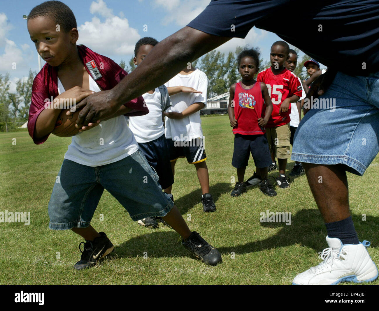 Jul 22, 2006; Riviera Beach, FL, USA; Six-year-old Bryan Howzell practices taking the football from Kenneth Payne during the Barrett Green Football camp at that Dan Calloway Recreational Complex. Payne is the center director of Wells Recreational center. Professional football players who worked with kids at the camp included Suncoast Alum, Barrett Green, Arizona Cardinals' Jack Bre - Stock Image