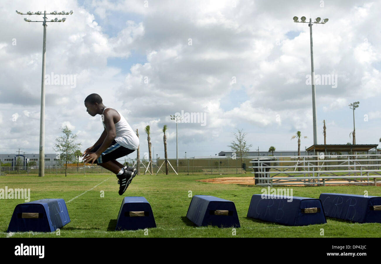 Jul 22, 2006; Riviera Beach, FL, USA; Fourteen-year-old Marquis Huggins leaps through obstacles during Barrett Green Footabll camp in Riviera Beach.  The exercise is intended to help the players work on their lateral movement, in order to improve their ability to jump and block passes. Professional football players who worked with kids at the camp included Suncoast Alum, Barrett Gr - Stock Image