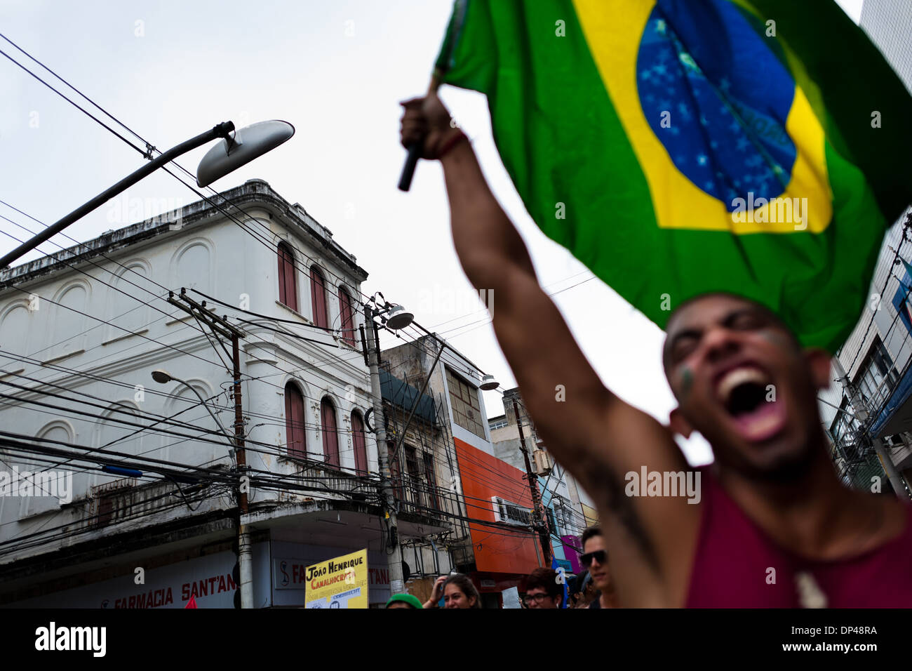 A radical protester, holding the Brazilian flag, screams during the protest march in Salvador, Bahia, Brazil. - Stock Image