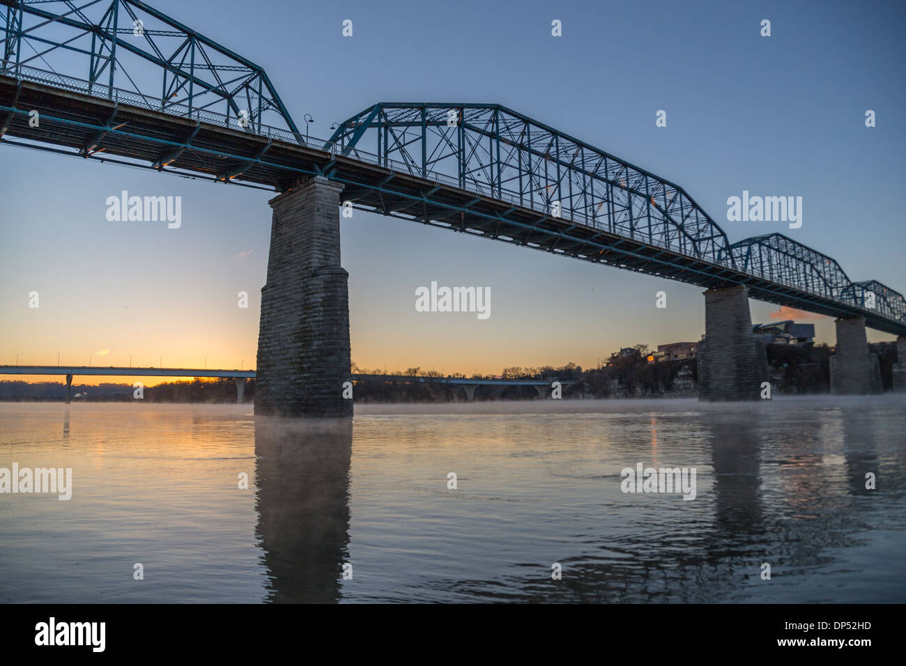 The sunrise reflects on the Tennessee River as steam rises under the Walnut Street Bridge on a very cold winter morning - Stock Image
