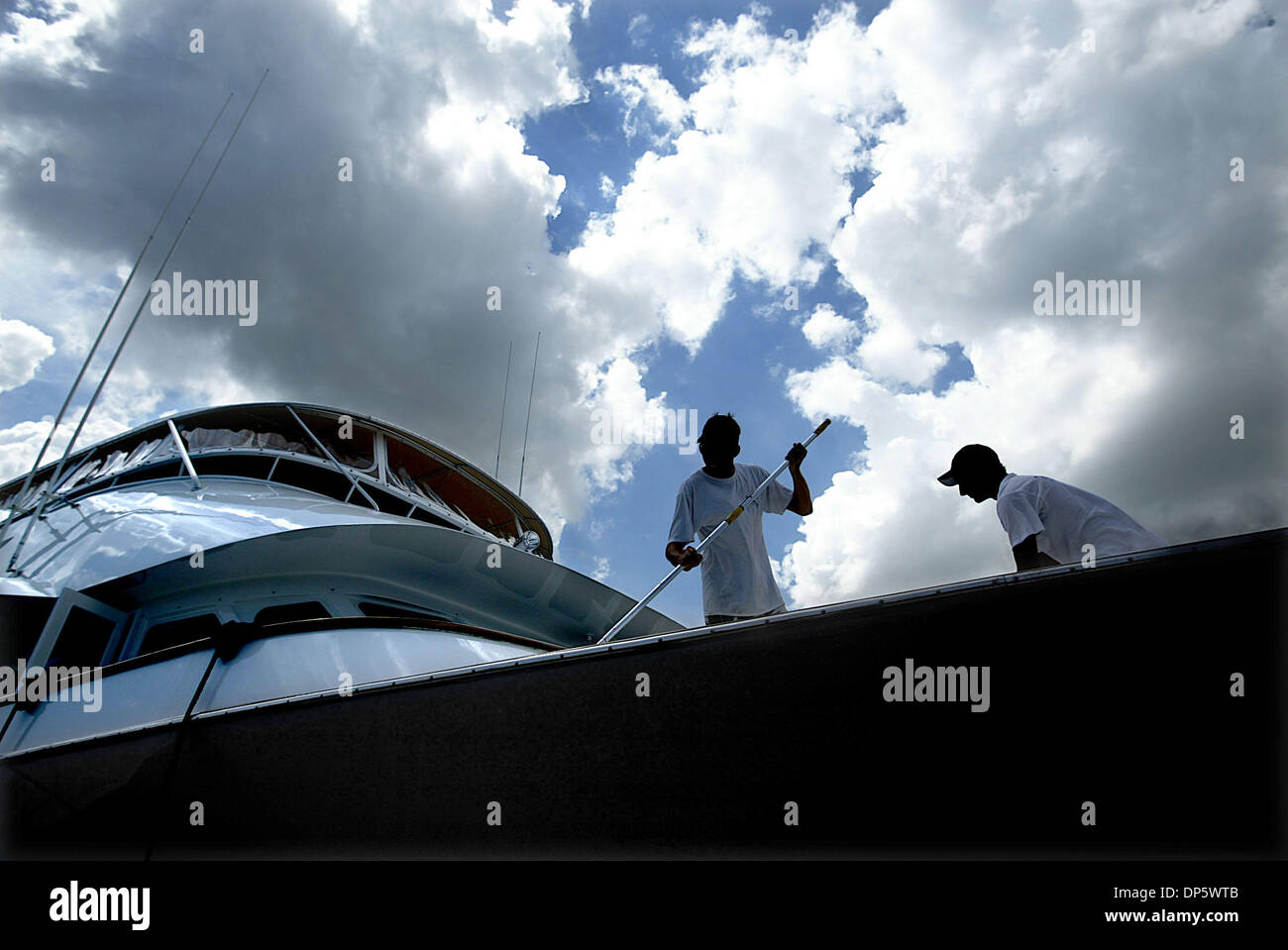 Sep 26, 2006; Palm Beach, FL, USA; Daniel Ross (L), 21, and his younger brother Alex, 19, work Tuesday afternoon to wash down the Azucar, a 100 ft. Poole Chaffe boat docked on Palm Beach Island.  The brothers, who live on Singer Island, have been detailing boats since their early teens.  They operate their own business called Ocean Spray Detailing and said, 'The money from the busi - Stock Image