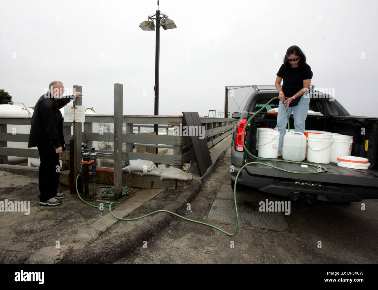 Sep 27, 2006; San Diego, CA, USA; JAMES MURPHY, left, and his wife, ANGELA, fill buckets with salt-water from Scripps Institute of Oceanography in La Jolla, in order to monthly change the water in their 240-gallon salt-water fish tank in their San Diego home.  Mandatory Credit: Photo by Laura Embry/SDU-T/ZUMA Press. (©) Copyright 2006 by SDU-T - Stock Image