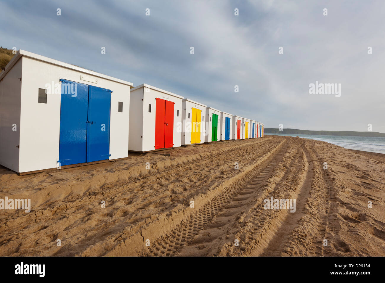 Beach huts in a row on Woolacombe Sands in North Devon, UK. - Stock Image