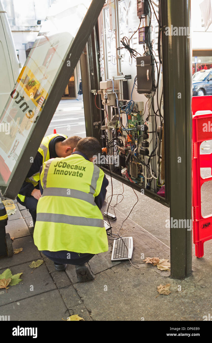 Engineers fix the inner workings of a bus stop poster site - Stock Image