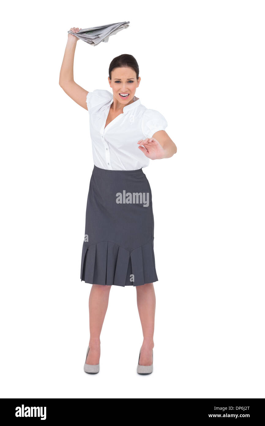 Angry stylish businesswoman throwing newspaper away - Stock Image