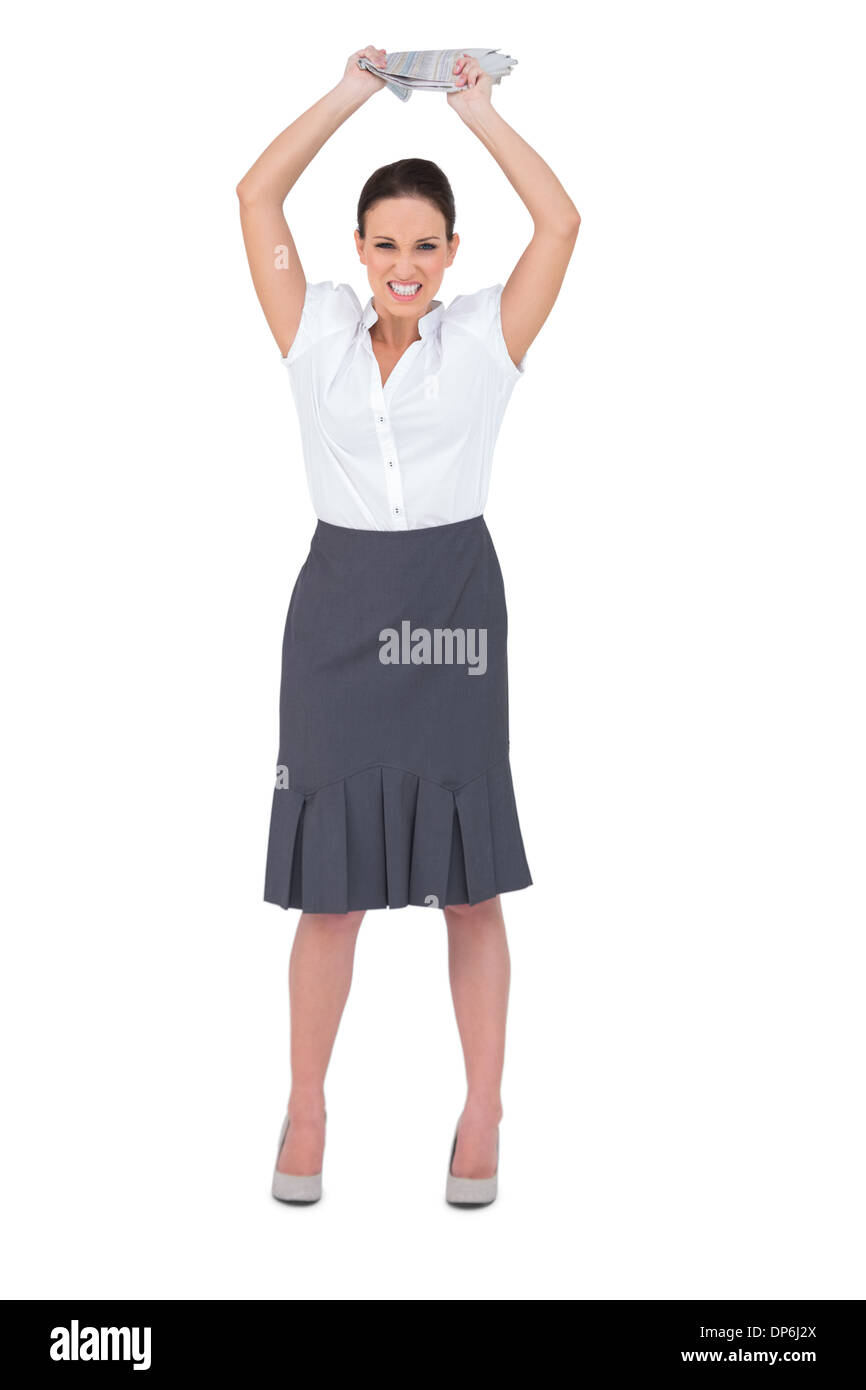 Angry smart businesswoman throwing newspaper away - Stock Image