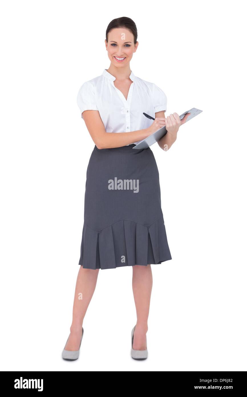 Beautiful businesswoman holding clipboard - Stock Image
