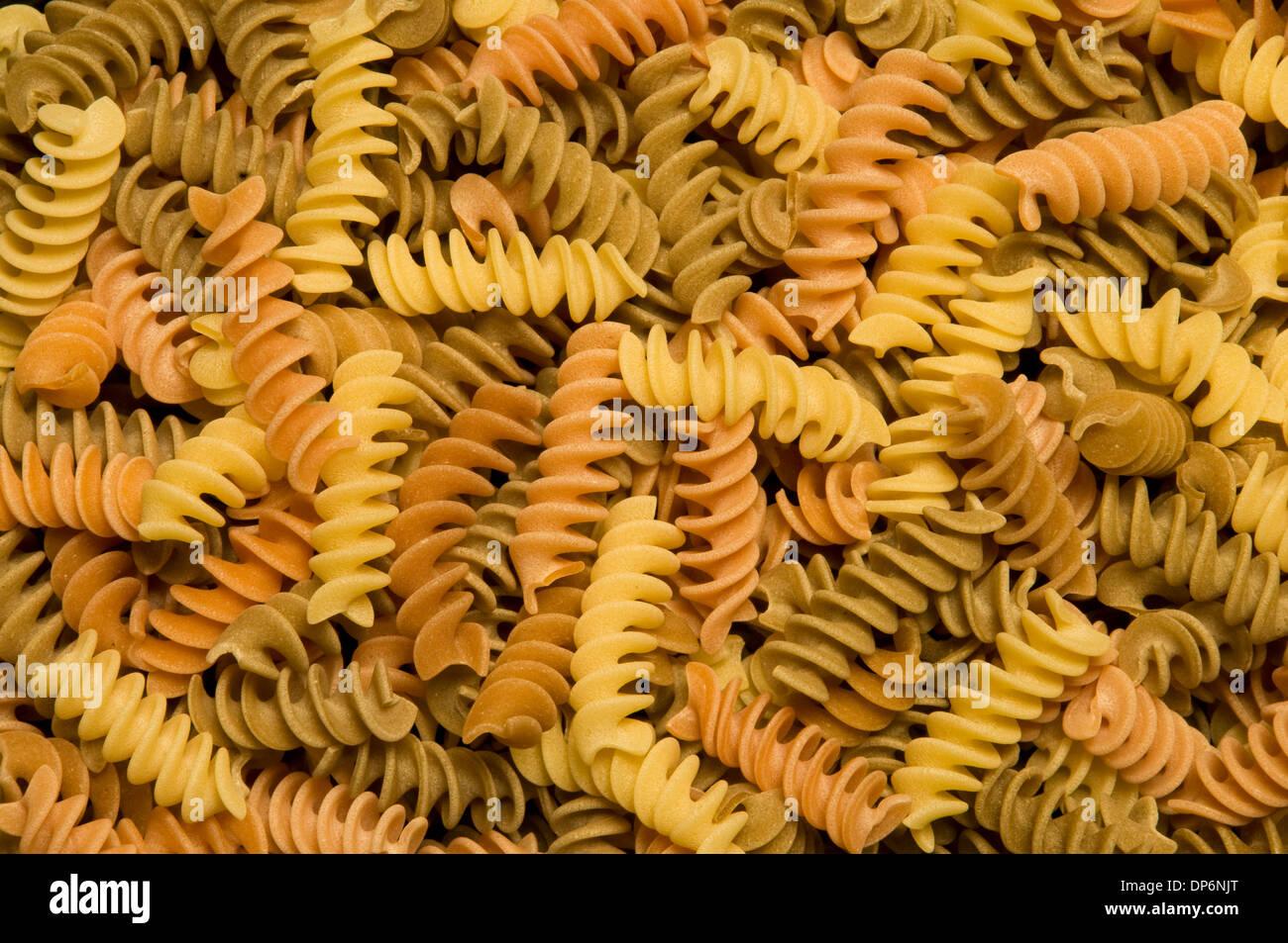 Uncooked multi-colored fusilli, corkscrew-shaped pasta - Stock Image