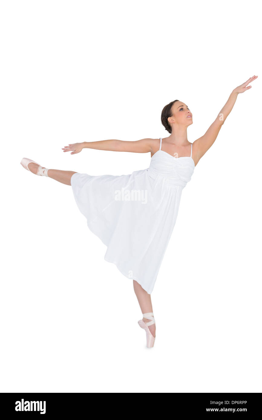Focused ballet dancer posing on her tiptoe while rising a leg - Stock Image