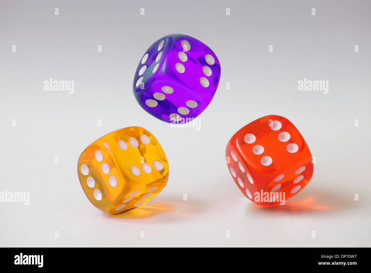 Three clear plastic dice with a six on every face tumbling on a plain white background - Stock Image