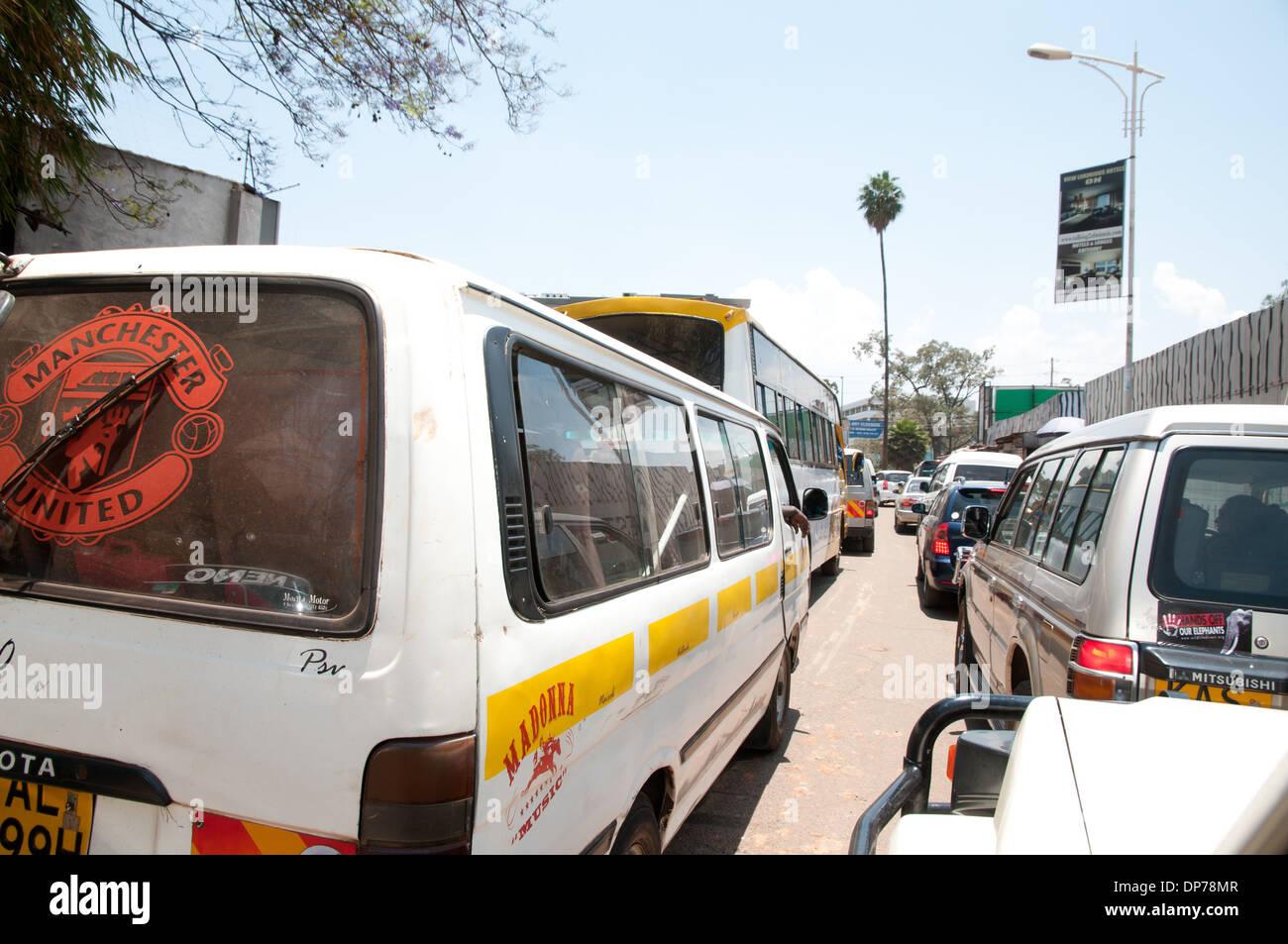 Traffic queue in Nairobi Kenya with Minibus matatu carrying logo for Manchester United in rear window - Stock Image