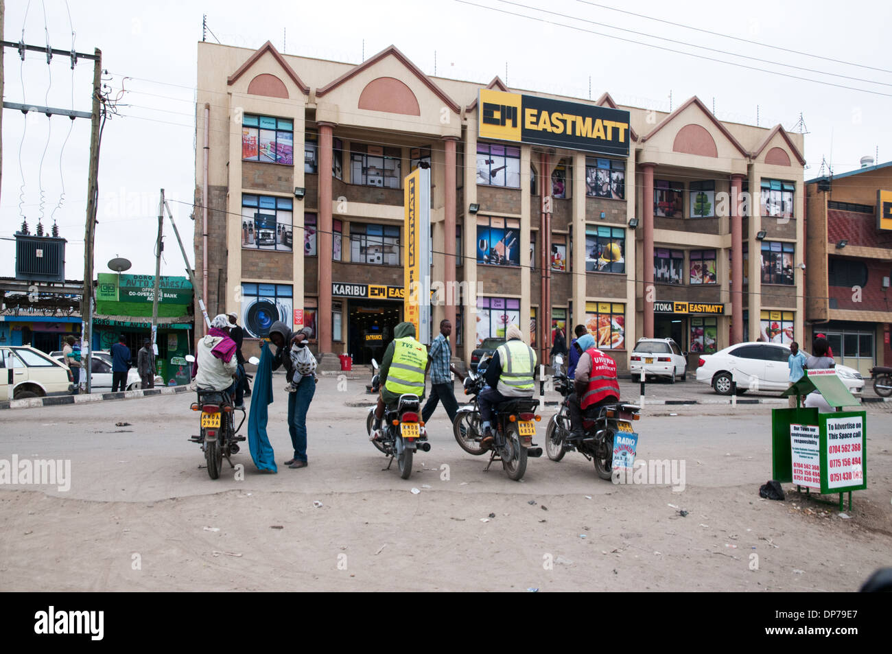 Motor cycle taxis await clients at Eastmatt supermarket on Nairobi Namanga Road Kaijado Kenya Africa - Stock Image