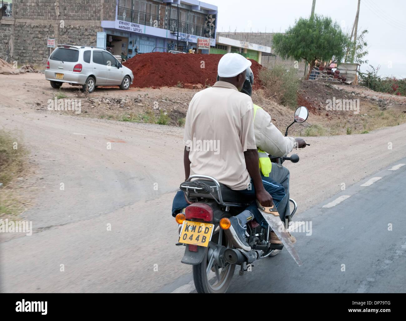 Motor Cycle Taxi with client carrying saw on Nairobi Namanga road at Kajiado Kenya Africa - Stock Image