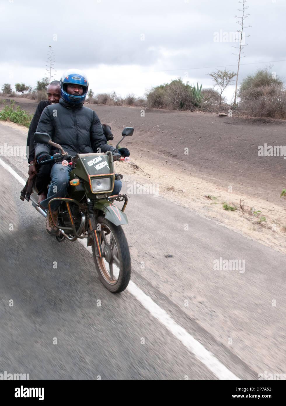Motor Cycle Taxi with client carrying a goat on Nairobi Namanga road south of Kajiado Kenya Africa - Stock Image