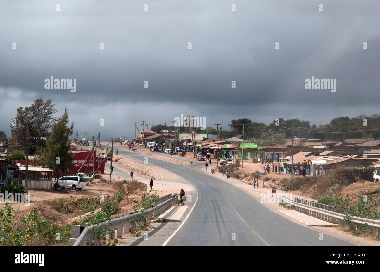 Village of Bissil or Bissel on Nairobi Namanga tarmac paved road Kenya Africa showing shops dukas people bridge and power lines - Stock Image