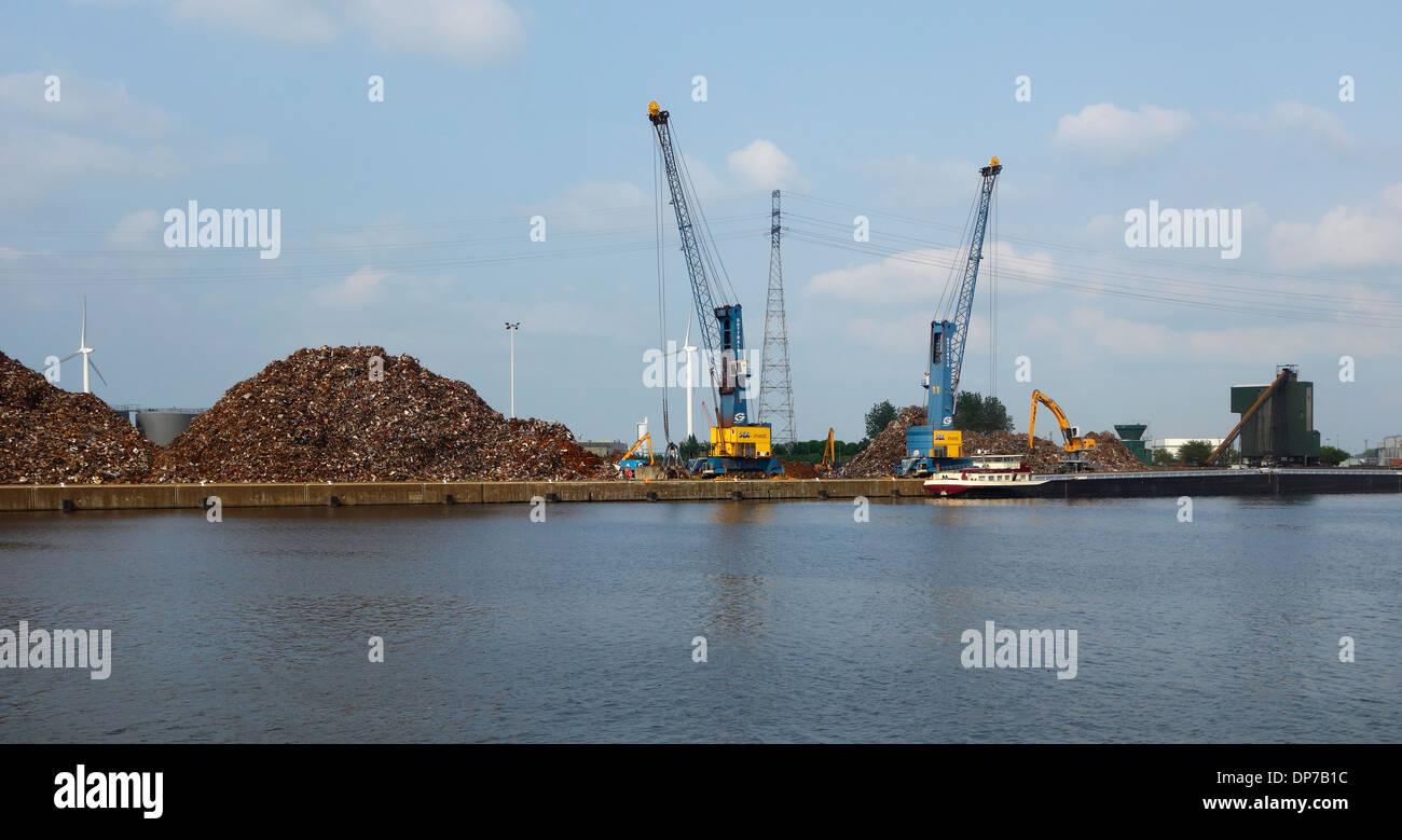 Dock cranes and heaps of scrap metal at Van Heyghen Recycling export terminal in the port of Ghent, East Flanders, Belgium - Stock Image