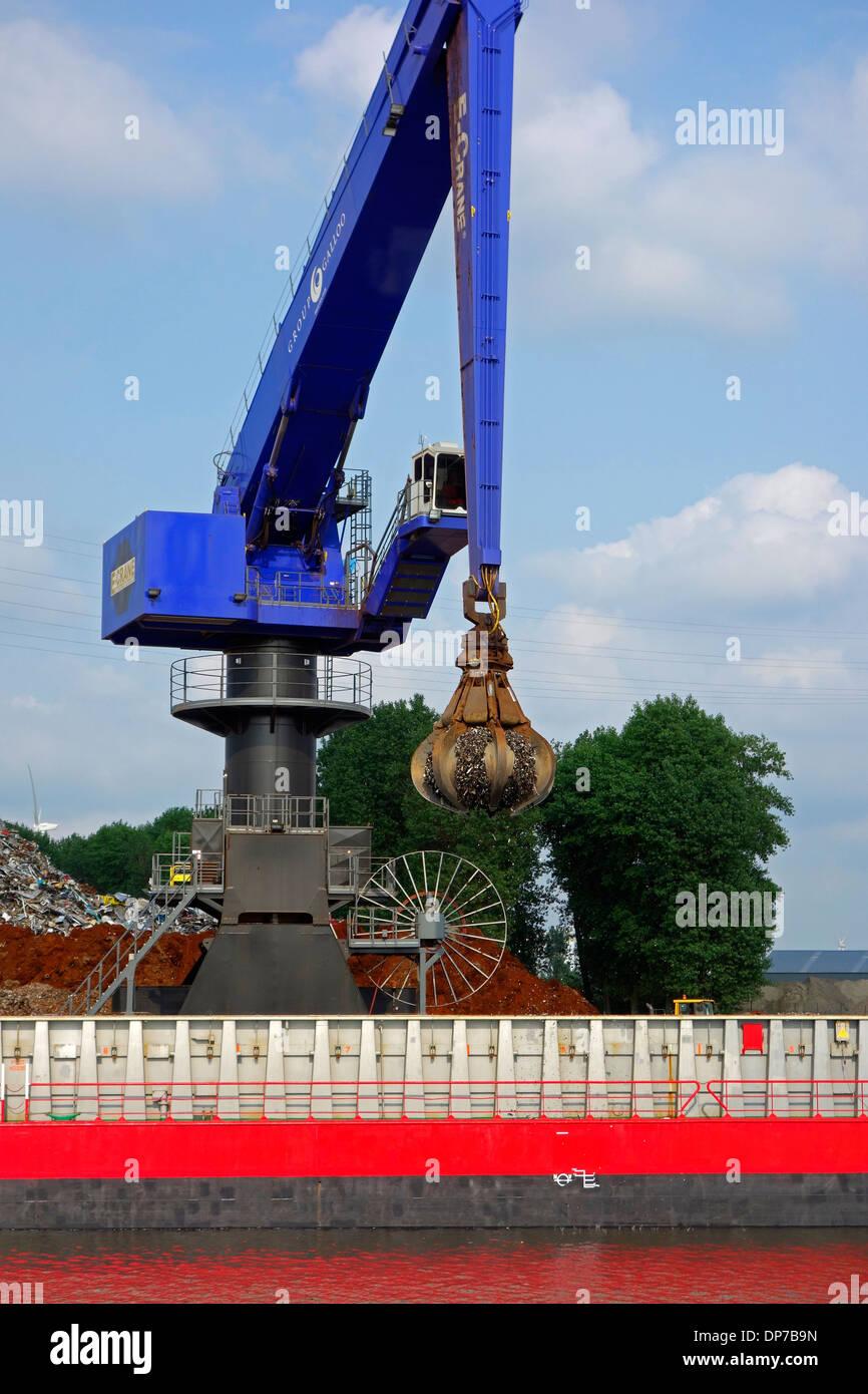 E-Crane, scrap crane loading recycled metal on cargo ship, Van Heyghen Recycling export terminal, Ghent port, Flanders, Belgium - Stock Image