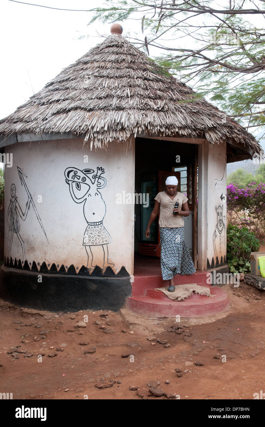 Mud and wattle rondavel with thatched roof and imaginative African art work mural at duka tourist stop Namanga Kenya Africa - Stock Image