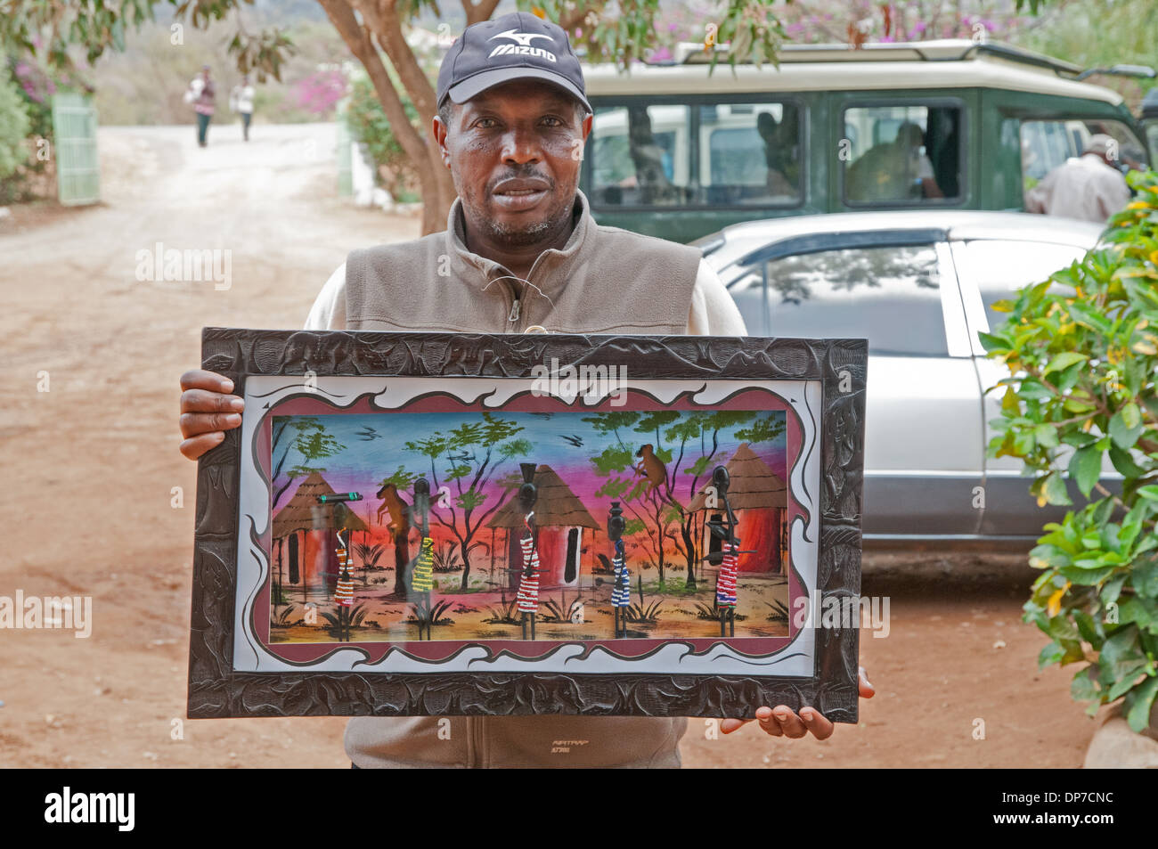 Man showing African painting in carved wooden frame depicting ...