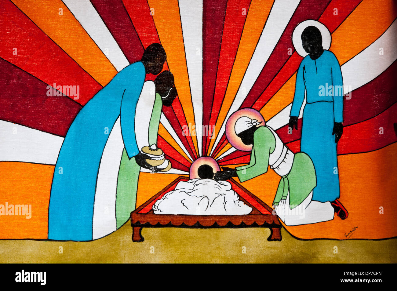 African batik showing crib with Christ Child Virgin Mary and Joseph with halos three wise men with gifts and sunset background - Stock Image