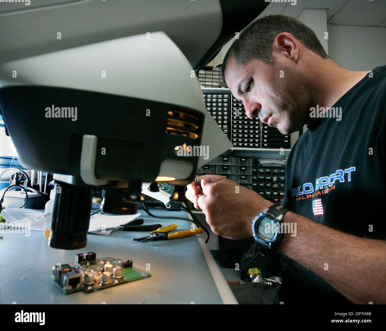 Aug 31, 2006; Rancho Bernardo, CA, USA; Sensoria Corp. senior engineering technican DAVID BOYETT assembles a small printed circuit board using a microscope to aid in soldering small parts.  Sensoria Corp. makes wireless networks that are used not only by the military but also by universities and  municipalities that want to offer wireless, high-speed Internet access outdoors.   Man - Stock Image