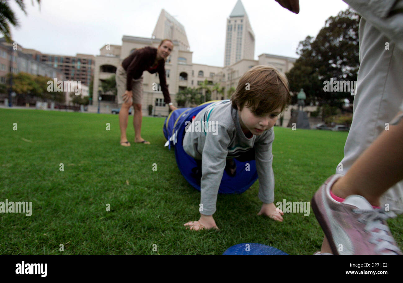 Nov 09, 2006; San Diego, CA, USA; CONNER ROLFE,  3,  exits a  collapsible tunnel as  board certified personal trainer Sean Mageau leads some downtown area children who meet for a play date in Pantajo Park (on G Street, near India St.) in exercises. The children's parents pay the trainer a nominal fee (he basically does it for free, having met the children as they played in the park - Stock Image