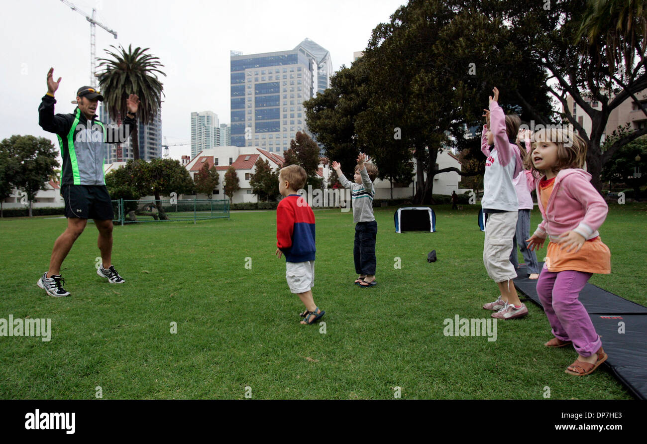 Nov 09, 2006; San Diego, CA, USA; Board Certified personal trainer SEAU MAGEAU leads some downtown area children who meet for a play date in Pantajo Park (on G Street, near India St.) in exercises. The children's parents pay the trainer a nominal fee (he basically does it for free, having met the children as they played in the park while he was coincidentally was training private c - Stock Image