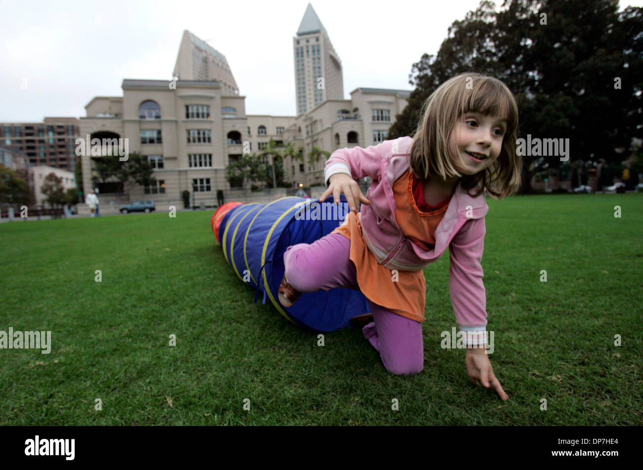 Nov 09, 2006; San Diego, CA, USA; MELODY RUTH, 6, exits a  collapsible tunnel as  board certified personal trainer Sean Mageau leads some downtown area children who meet for a play date in Pantajo Park (on G Street, near India St.) in exercises. The children's parents pay the trainer a nominal fee (he basically does it for free, having met the children as they played in the park wh - Stock Image