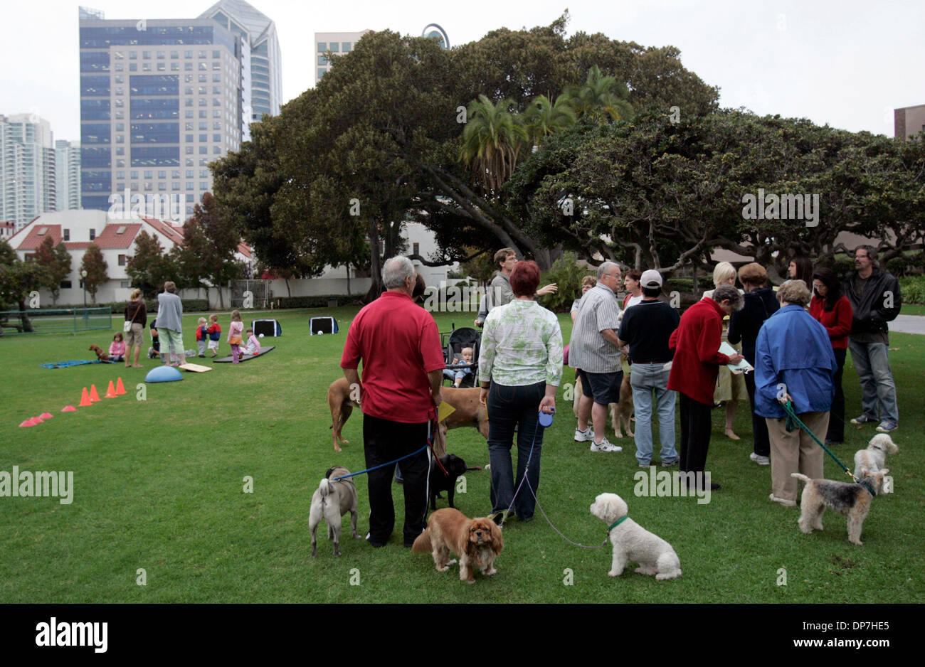 Nov 09, 2006; San Diego, CA, USA; Pet owners gather around children's parent's who use the park, as  board certified personal trainer Sean Mageau leads some downtown area children who meet for a play date in Pantajo Park (on G Street, near India St.) in exercises. The parent's are trying to get play equipment for the park, and might want the pet owners use of the park curbed in fav - Stock Image