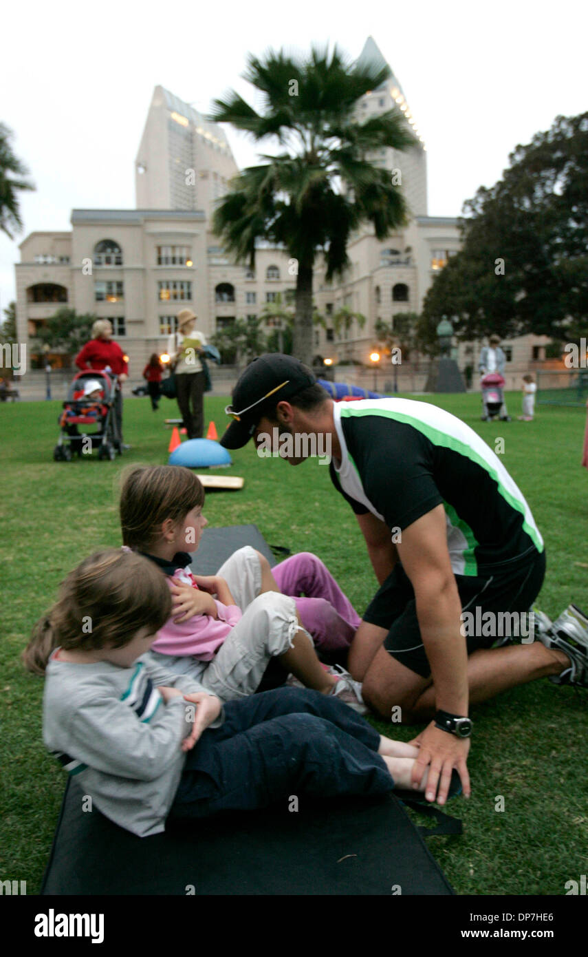 Nov 09, 2006; San Diego, CA, USA; Board Certified personal trainer SEAU MAGEAU leads some downtown area children who meet for a play date in Pantajo Park (on G Street, near India St.) in exercises. On the left are CONNOR ROLFE  (foreground) and MARIA MEOLA, 6. The children's parents pay the trainer a nominal fee (he basically does it for free, having met the children as they played - Stock Image