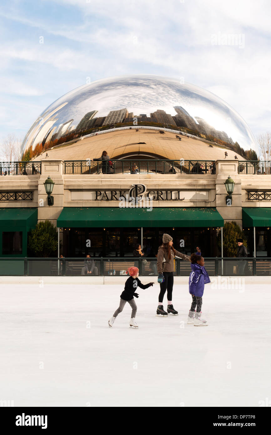 People ice skate at the McCormick Tribute Plaza and Ice Rink with the Cloud Gate sculpture behind. - Stock Image
