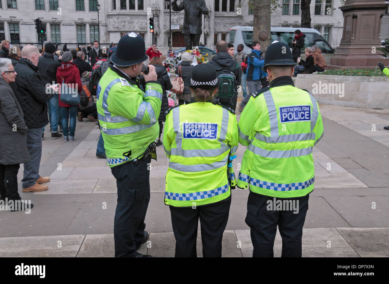 Three Metropolitan Police officers in Parliament Square, London, UK. - Stock Image