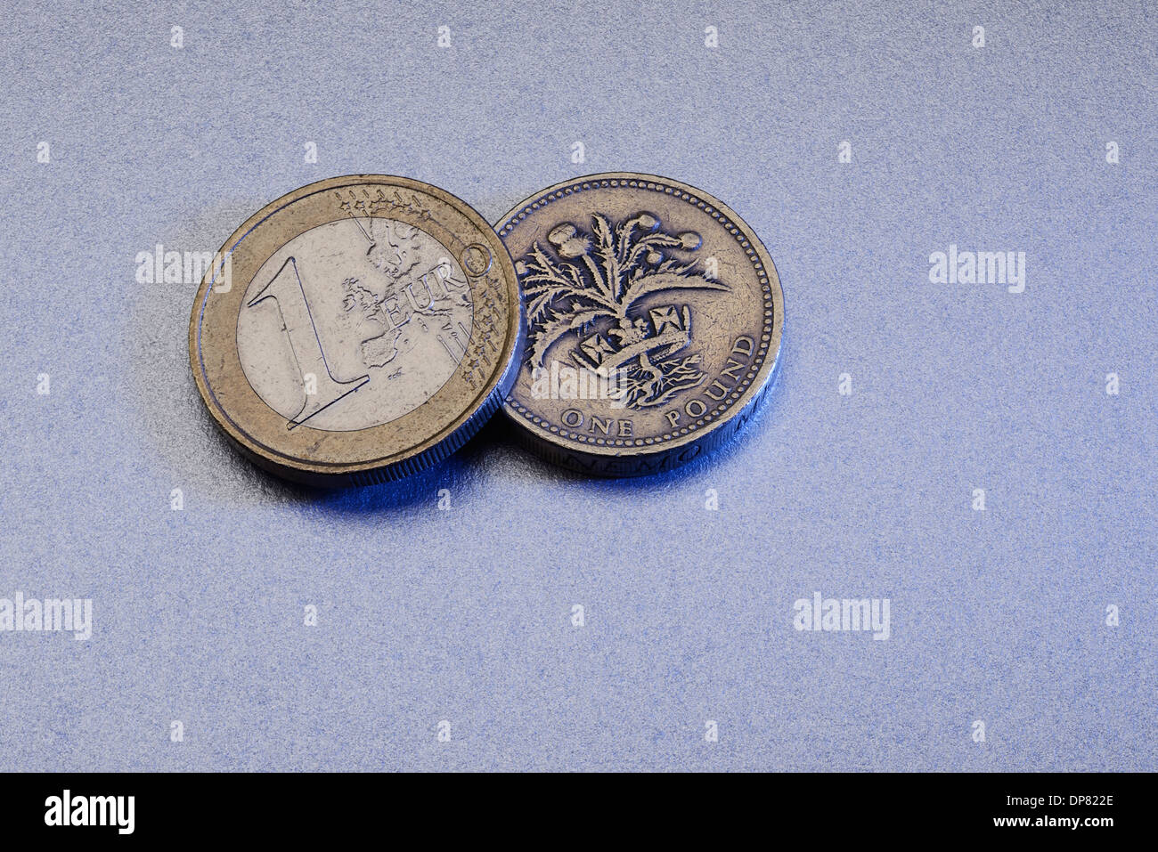 One Euro coin and a one pound coin - Stock Image