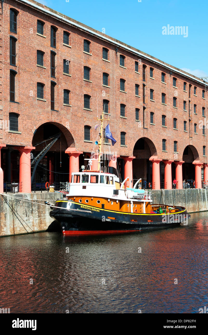 An old tug boat moored outside the refurbished warehouses at the Albert Dock complex in Liverpool, England, UK - Stock Image