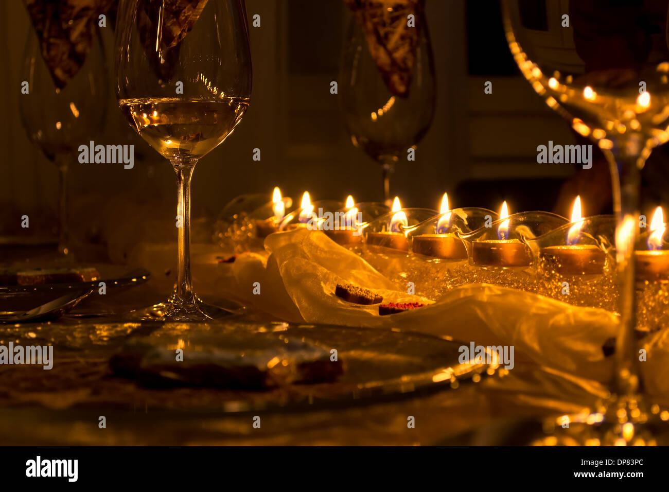 Solemn Dining Table, wine glasses in the candlelight - Stock Image