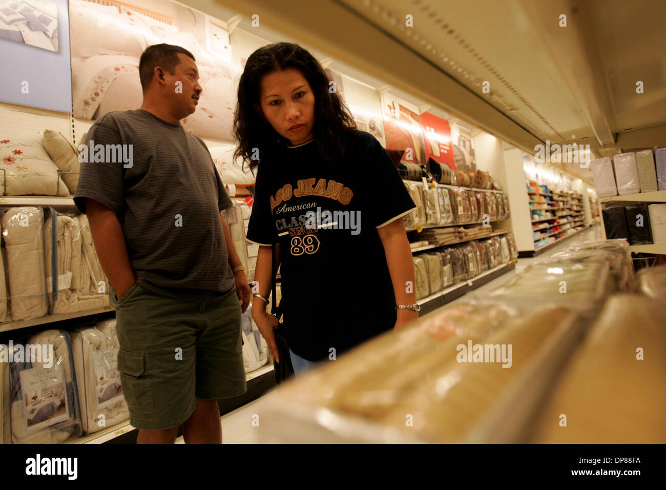 (Published 9/29/2005, B-2:2; B-10:1) Julieto, left, and Jean Apelacion (cq) are a bit overwhelmed at the choices as they shop Wednesday afternoon for linens. The family is being sponsored by the Church of St. Luke in El Cajon, who bought the bedding and towels for them. Peggy Peattie photo - Stock Image