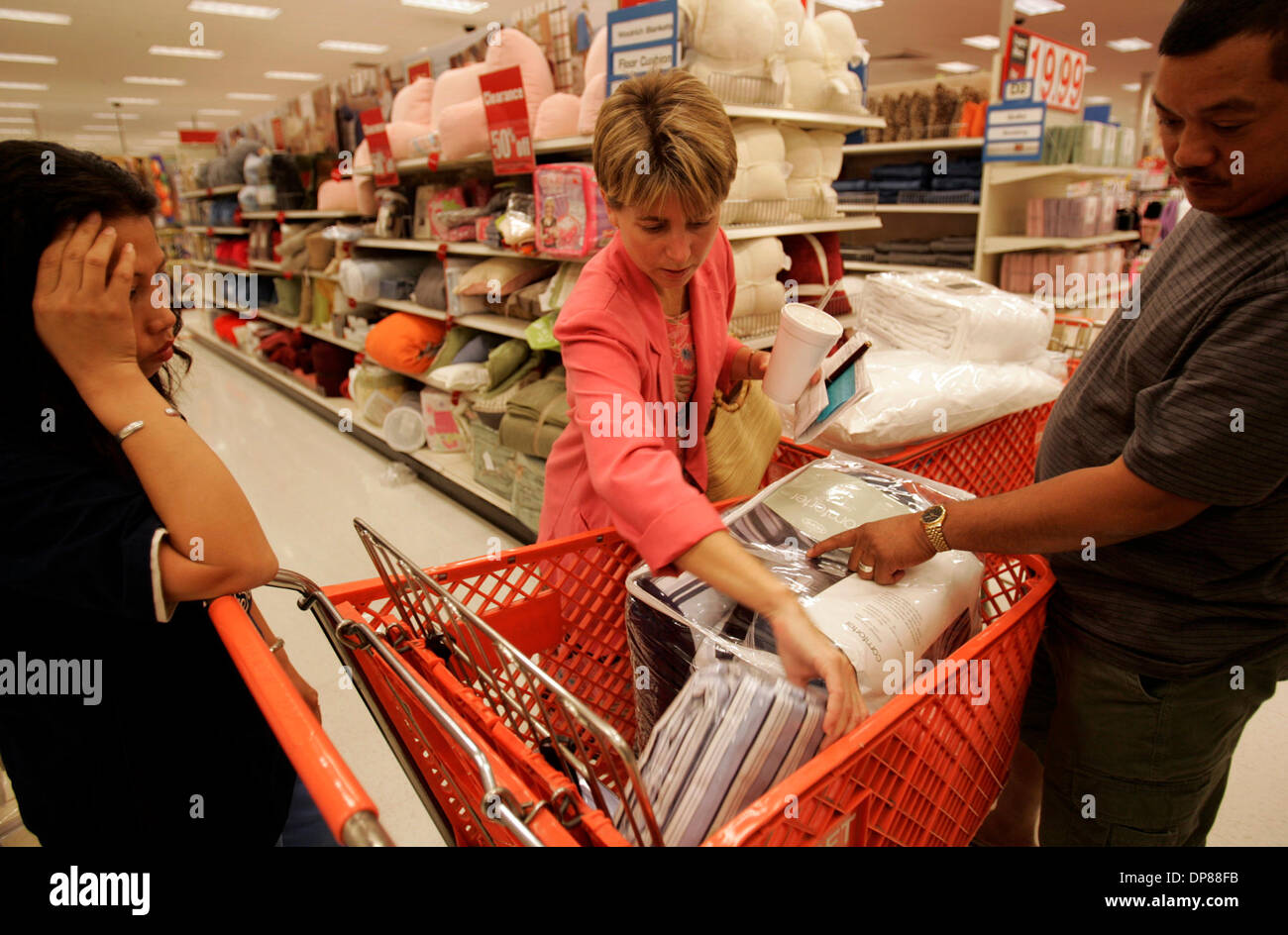 (Published 9/29/2005, B-1) Jean, left, and Julieto, right Apelacion (cq) are a bit overwhelmed at the choices as they shop Wednesday afternoon (9/28/2005) for linens with Pam Fleming, center, of the Church of St. Luke in El Cajon, which is sponsoring the former residents of New Orleans. The church bought the bedding and towels for the Apelacion family. Peggy Peattie photo - Stock Image