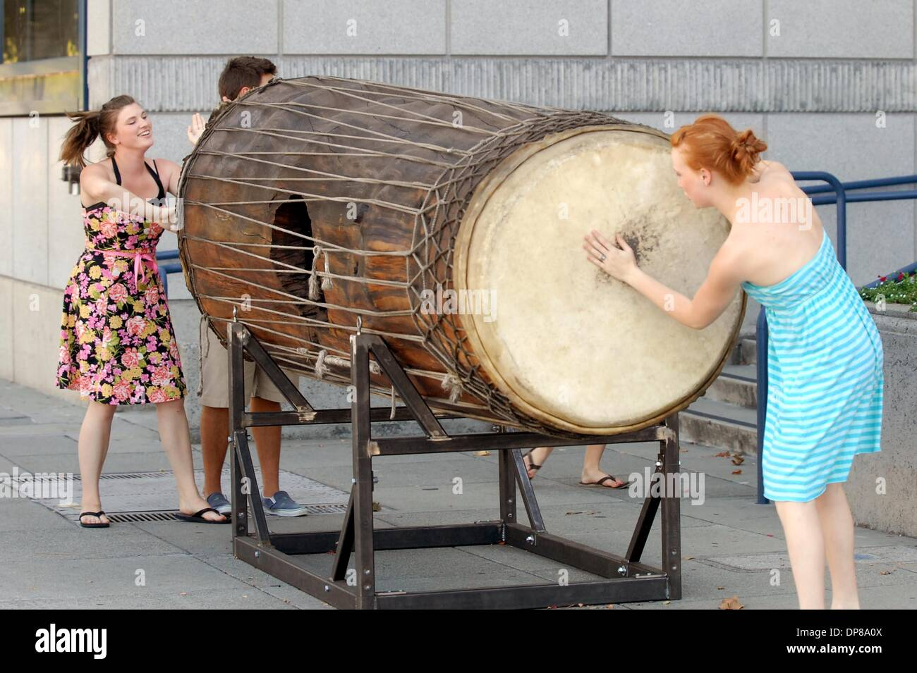 Amanda Denison, Walnut Creek, left, and Erin Searfus, Pittsburg, get into the beat of a doubled-sided drum outside of the Lesher Center for the Arts in Walnut Creek Calif., Tuesday, July 31, 2007. Two giant drums have been installed outside the Lesher Center for the Arts and are part of a Bedford Gallery exhibit. The drums belong to artist and filmmaker Banker White. The double-sid - Stock Image